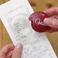Close-up of a person using the magnifier to read a receipt