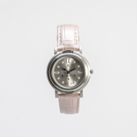 Front view of tactile watch with strap buckled up against a white background