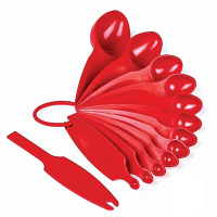 Top view of fanned out red measuring spoons  against a white background