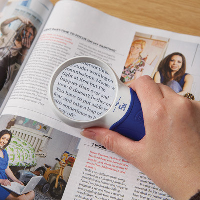 Close-up of a person using the Coil ATMAX 5× hand magnifier to read a magazine