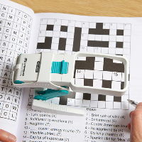 Close-up of a person using the magnifier to do a crossword