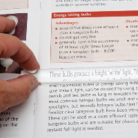 Close-up of a person using the magnifier to read a magazine