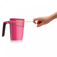 A person trying to tip a pink anti-spill suction mug using a rubber band