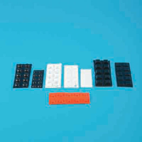 A selection of black, white and orange self-adhesive rubber dots against a blue background