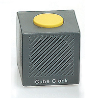 A simple grey cube shaped alarm clock with a large yellow button on top
