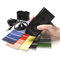 A person using the Talking Colour Detector to detect colours of paint sample cards