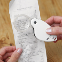 Close-up of a person using the 10× magnifier to read a receipt