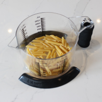 Two black pan pickles holding a measuring jug containing dry pasta in place on a worktop