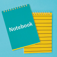 Two notebooks, one open showing yellow paper and one closed showing the cover which says Notebook