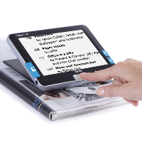 Compact 7HD video magnifier with black text on a white background on screen above a magazine