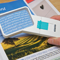 Close-up of the Okolux Mobil Plus LED angled 2.5× 6,500K hand magnifier over a magazine