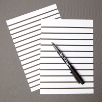 Close-up of lined paper with a pen