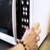Close-up of a person using microwave oven function buttons