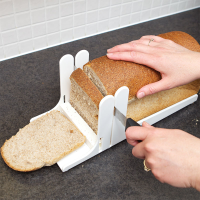 A person slicing bread using a white bread slicing guide with tactile markings