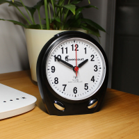 The clock sits upon a table top.