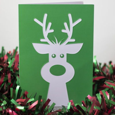 Embossed reindeer Christmas card surrounded by tinsel