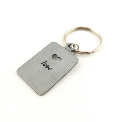 Keyring at an angle with a punched heart-shaped hole and the word 'love' engraved underneath