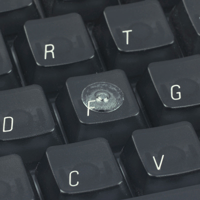 A clear loc dot attached to the F key on a computer keyboard