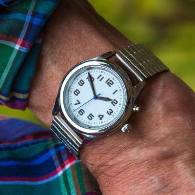 Talking watch with white face, clear black numbers and hands and a stainless steel bracelet strap