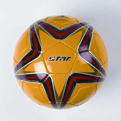 Yellow size four football with the star-shaped red and black printed design visible