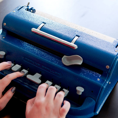 A woman's hands on the keys of a Perkins brailler
