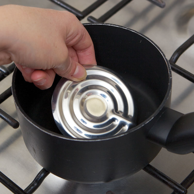 Close-up of a person putting the Boil alert into a pan