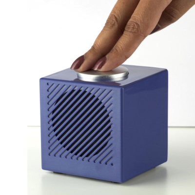 An angled simple blue cube shaped alarm clock with a large silver button on top