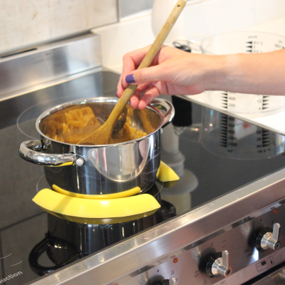 Yellow pan pickles holding a pot in place on an induction hob while food is stirred