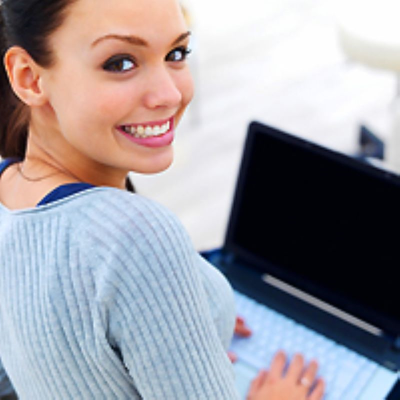 Young adult sitting with an open laptop