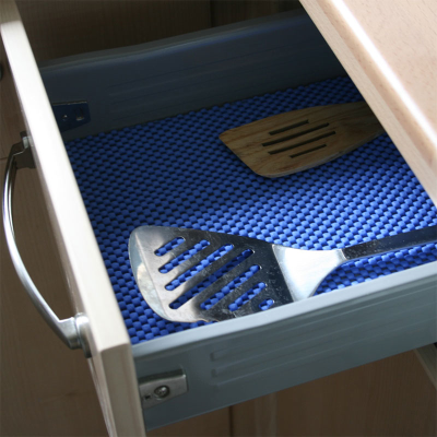 Non-slip material being used in a kitchen drawer with utensils placed on top