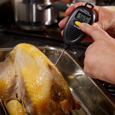 Thermometer being used to check temperature of a roast chicken