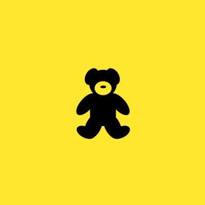 Black teddy bear on a yellow background.