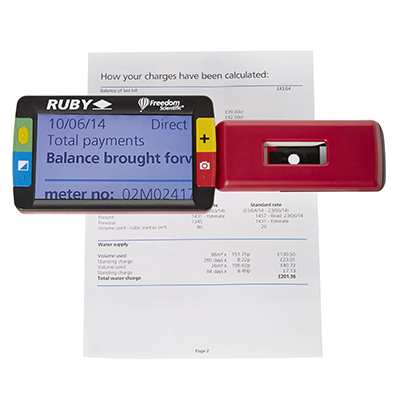 Ruby handheld magnifier showing the enlarged text of a household utility bill beneath it