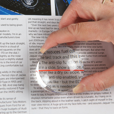 Close-up of person using magnifier on a page of text