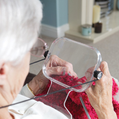 A woman holding the magnifier to help with knitting