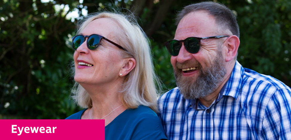 Couple sitting in the garden laughing and wearing tinted eyeshields