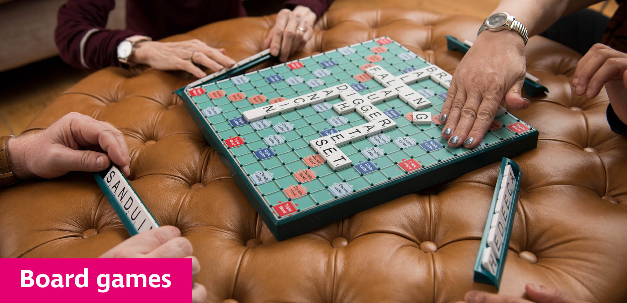 Group of friends playing large print Scrabble