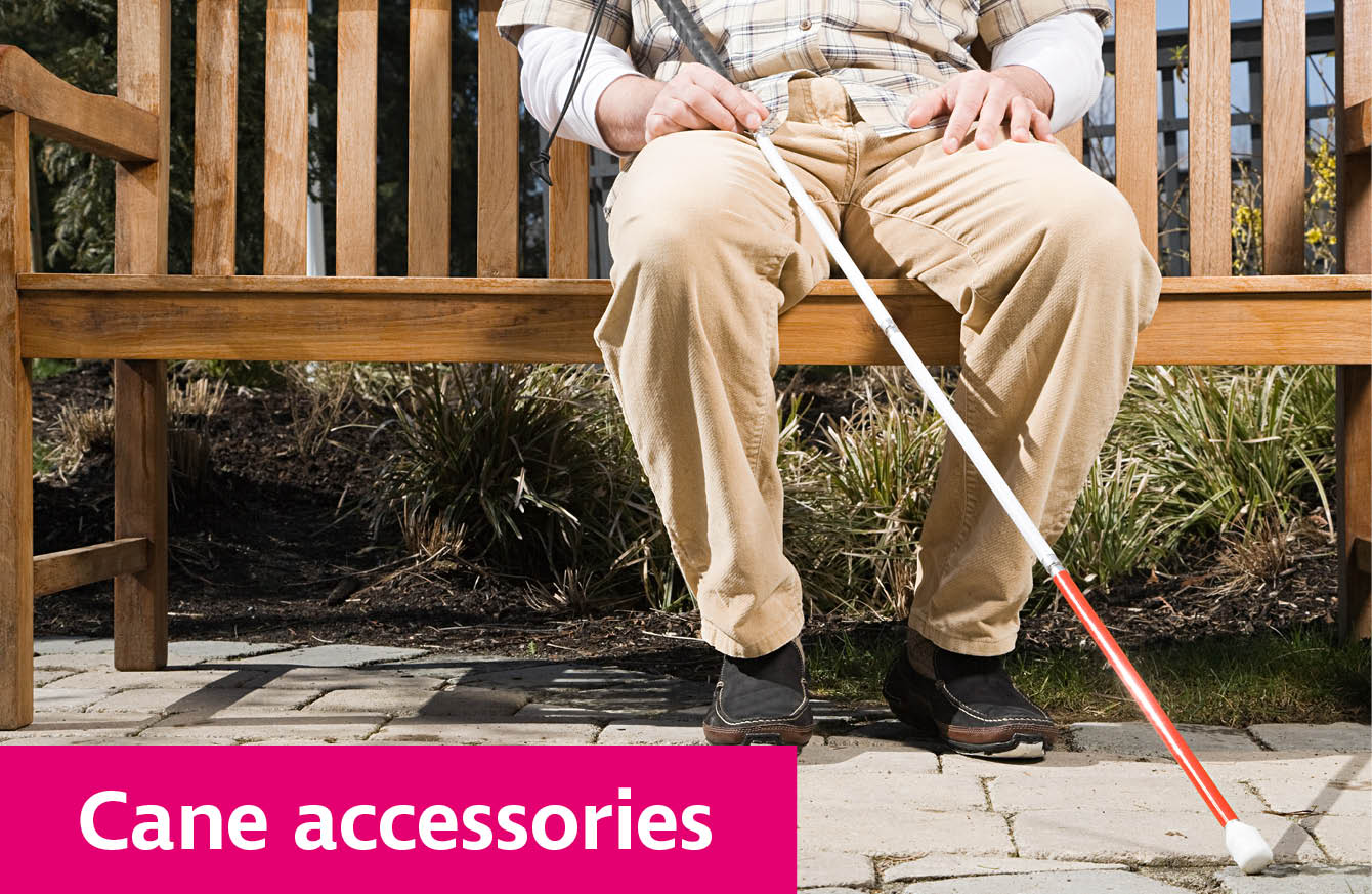 Man sitting on a bench, holding a deafblind long cane.