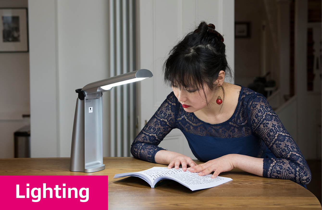 Woman using a desk light to read a book