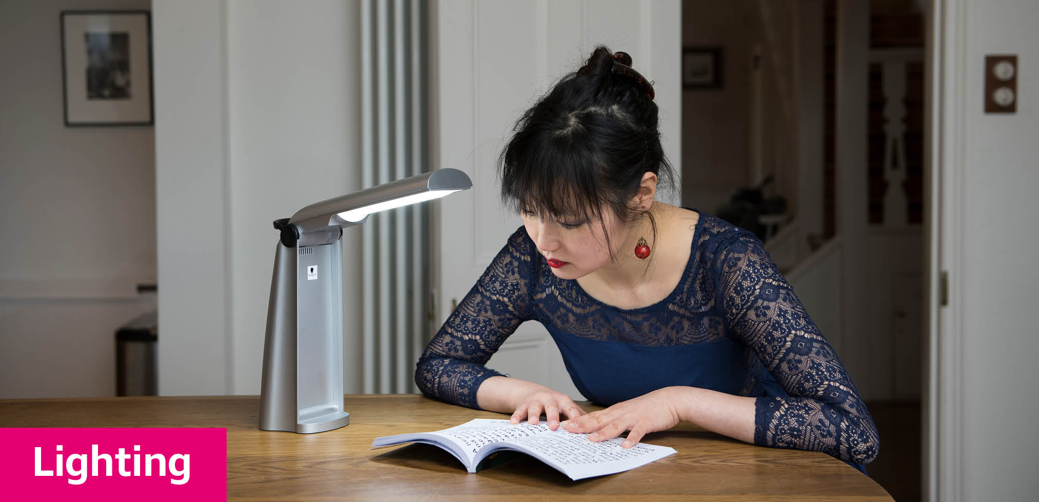 Lady sitting at table with desk light to help read her book