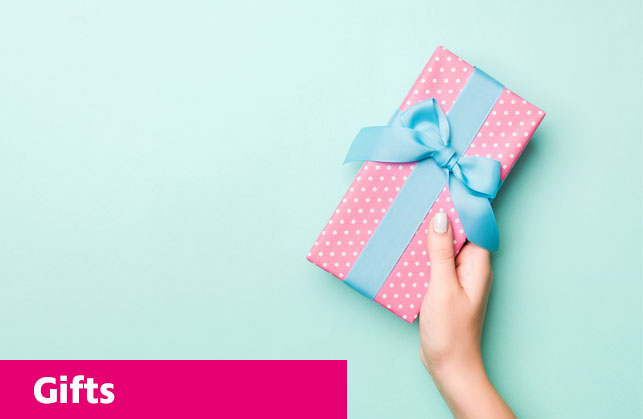 A gift wrapped in pink paper with white polkadots and a blue ribbon.