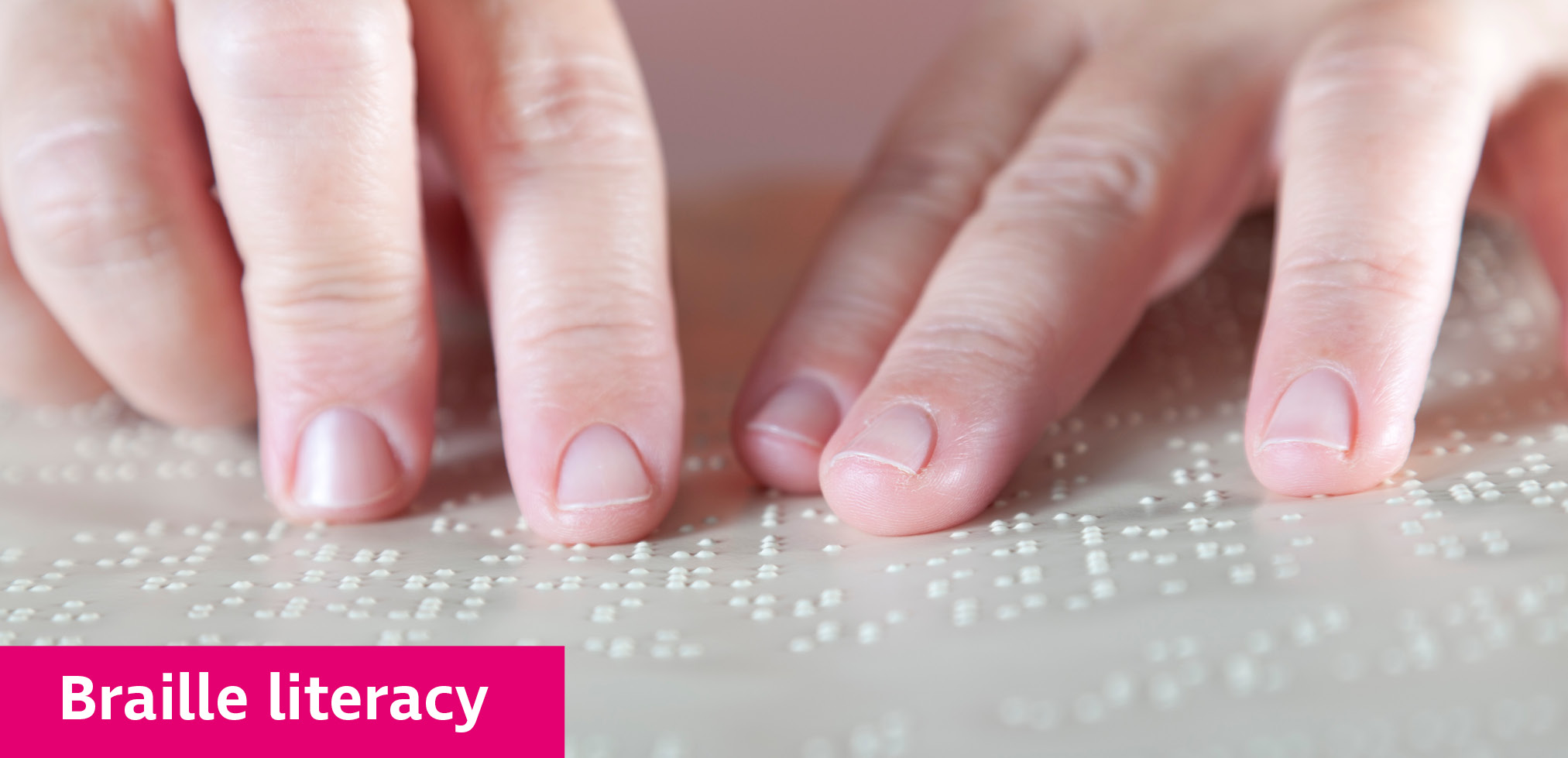 Hands reading a page of braille.
