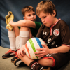 Teammates sitting on the sidelines holding a Rainbow blind football.