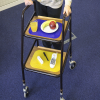 a person using a walking frame with a mat on each tray