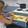 A woman using the mat along with a Dycem jar opener to open a jar