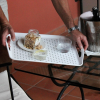 Tray being held at an angle with two glasses, a jar and a plate secured by the anti-slip material