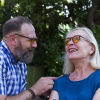 A woman and man sitting in the garden wearing Elipse eyeshields with grey filters