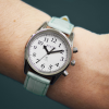 Small radio controlled taking watch with silver case, white face and mint strap on a wrist