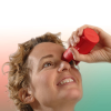 A woman using an orange eye-drop dispenser