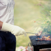 Close-up of a person using the gloves  on a barbecue